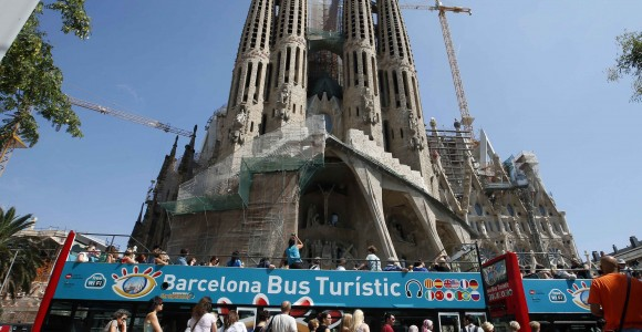 People queue up at a city tour bus stop in front of the Basilica Sagrada Familia in Barcelona