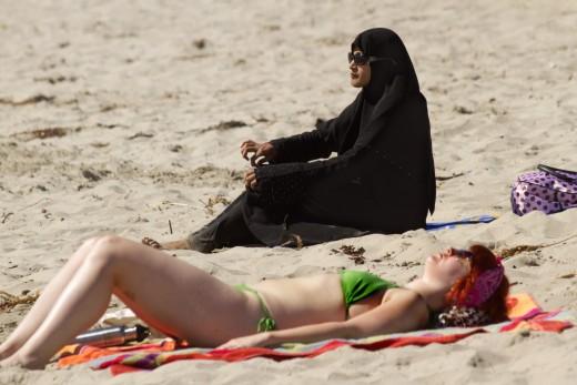 Ортодоксальная мусульманка и туристка из Европы на египетском пляже
