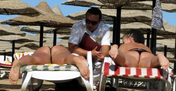 Туристки і службовець готелю на пляжі в Хургаді