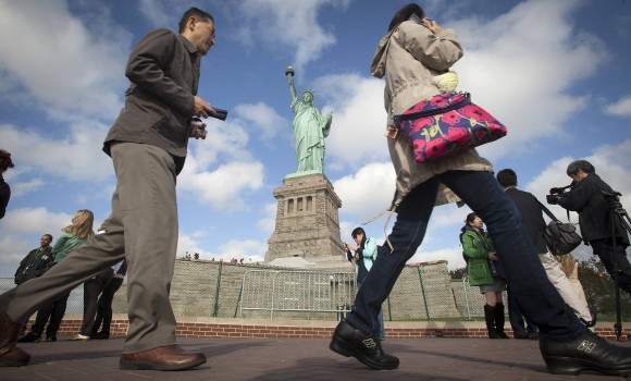 People walk past the Statue of Liberty on Liberty Island in New York. REUTERS