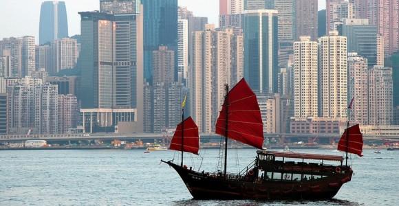 Традиційний китайський човен джонка в затоці Гонконга на тлі модерних хмарочосів