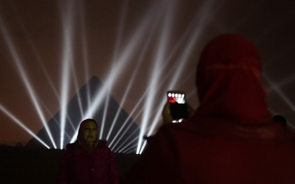 A woman photographs her friend in front of the Great Pyramids illuminated for New Year's Eve in Giza, near Cairo, Egypt late Thursday, Dec. 31, 2015. (AP Photo/Maya Alleruzzo)