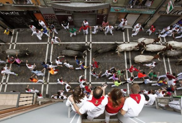 epa05416438 Bulls from the ranch Jose Escolar Gil run past revelers through the Estafeta Street during the third bull run of the Festival of San Fermin 2016 in Pamplona, Spain, 09 July 2016. At least two people were gored during the bull run. The festival, locally known as Sanfermines, is held annually from 06 to 14 July in commemoration of the city's patron saint. Hundreds of thousands of visitors from all over the world attend the fiesta. Many of them physically participate in the highlight event - the running of the bulls, or encierro - where they attempt to outrun the bulls along a route through the narrow streets of the old city. EPA/JESUS DIGES