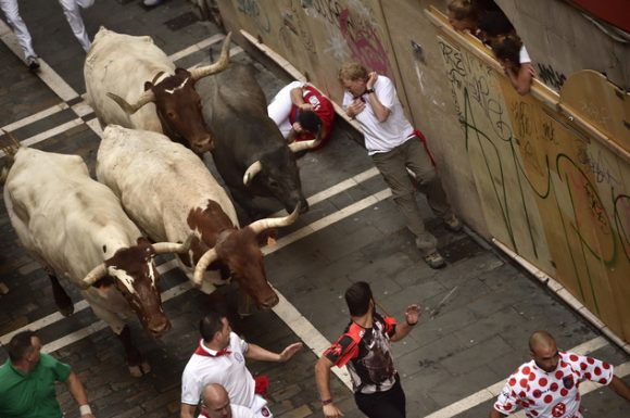 Revelers run with Jose Escolar Gil's fighting bulls as they head towards Estafeta street during the third running of the bulls at the San Fermin Festival, in Pamplona, northern Spain, Saturday, July 9, 2016. Revelers from around the world flock to Pamplona every year to take part in the eight days of the running of the bulls. (AP Photo/Alvaro Barrientos)