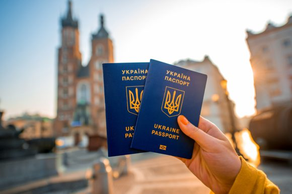 Female hands holding Ukrainian abroad passports on the Krakow city center background. Traveling to Europe from Post-Soviet countries or emigration to Europe concept